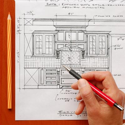 hand holding pen over kitchen cabinet plans