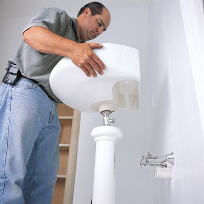 man installing pedestal sink in bathroom