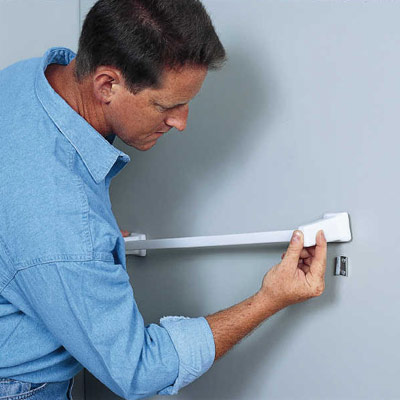 man anchoring towel bar in bathroom