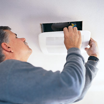 man installing bathroom ventilation fan