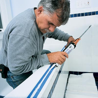 man caulking around bath tub