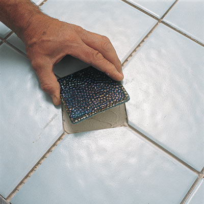 hand placing ceramic tile on bathroom floor