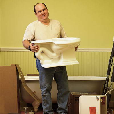 man holding new toilet before installing it in bathroom