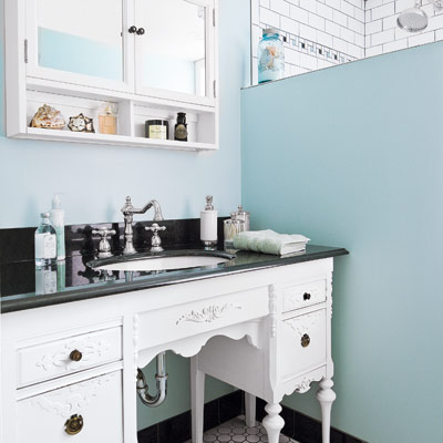 vintage bathroom with blue walls and vintage desk vanity with sink