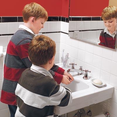 children washing up at a bathroom sink