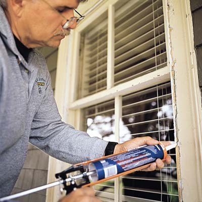 man sealing window frame with caulk