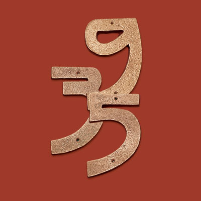 copper house numbers in a classic Craftsman-style typeface