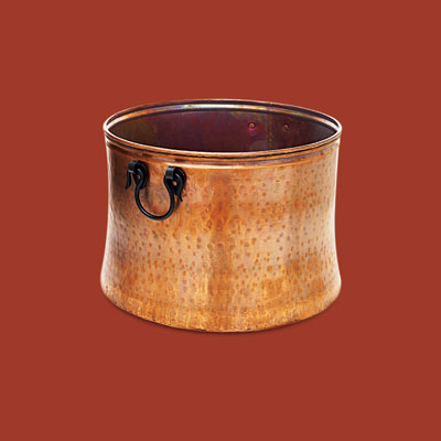 a hand-hammered copper bucket for storing firewood