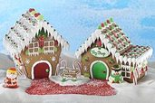 a pair of gingerbread houses with Santa and Frosty against a blue sky background
