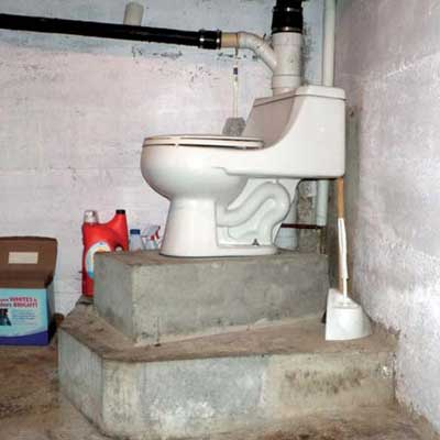 a toilet in a basement mounted about two feet off the floor