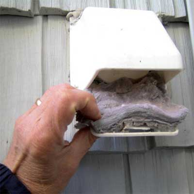 a dryer vent showing the screen being removed to reveal a massive coating of lint