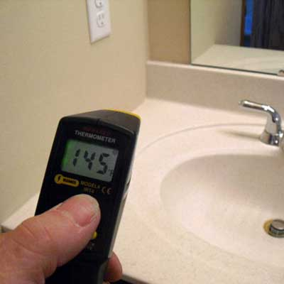 a point-and-shoot thermometer in the bathroom revealing the temperature to be 145 degrees