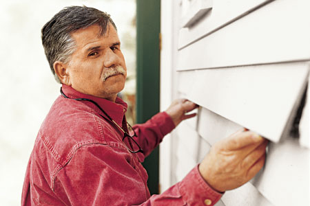 man replacing damaged clapboard with new one