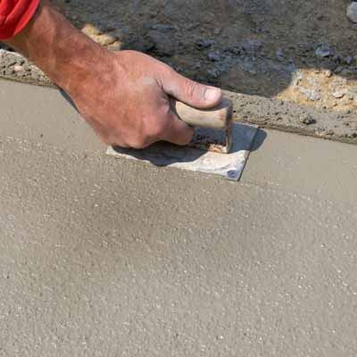 man laying concrete pathway