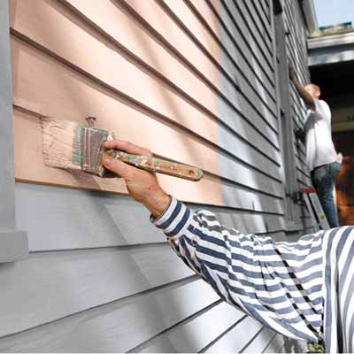man painting house exterior siding