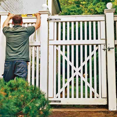 man checking fence and gate level
