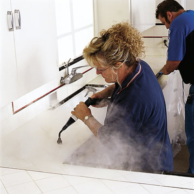 man and woman power cleaning tile grout