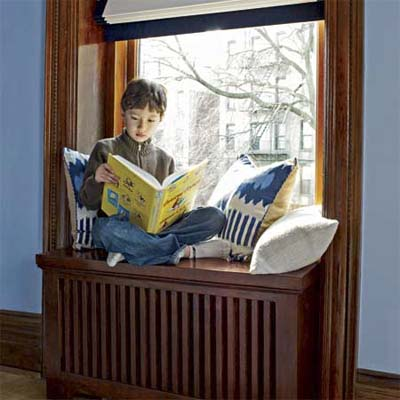 child reading on a radiator cover window seat
