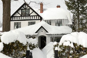 house and trees burdened by extreme snow fall