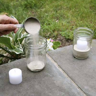 hand filling jar with sand and candle