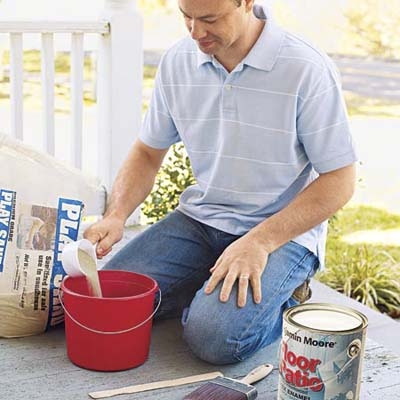 man adding sand to paint mixture
