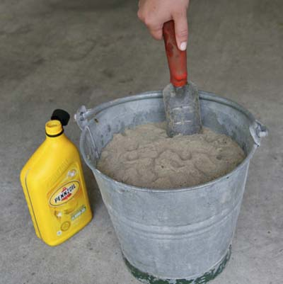 hand dipping garden tool in bucket of sand