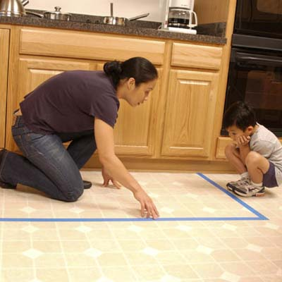 child home safety, child-proofing, and accidental injury prevention in the kitchen: woman mapping out kitchen stove area with child