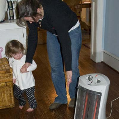 child home safety, child-proofing, and accidental injury prevention in the living room: woman guiding girl away from space heater