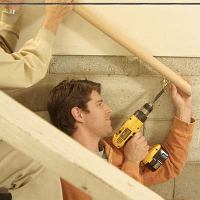child home safety, child-proofing, and accidental injury prevention in stairways and staircases: man using drill to secure staircase rail