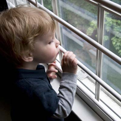 child home safety, child-proofing, and accidental injury prevention near windows: boy looking out window