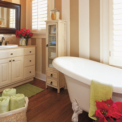 master bathroom with striped walls and claw foot tub in craftsman style cottage
