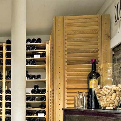 louvered panels disguising the air conditioner in this remodeled basement wine celler