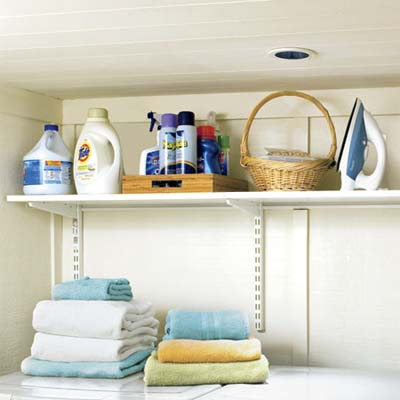 adjustable shelves built above the corner laundry nook built in this remodeled basement