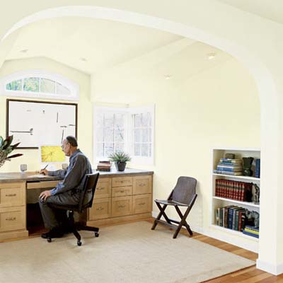 a large open archway separating the office and library in this attic remodel
