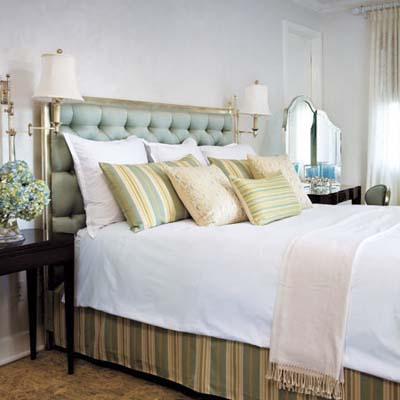 bedroom features cushioned headboard, patterned pillows and vanity mirror