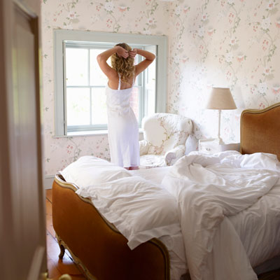woman stretching in bedroom after good night's sleep