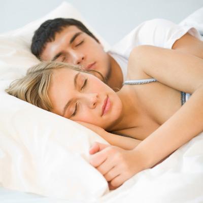 man and woman sleeping peacefully on new mattres