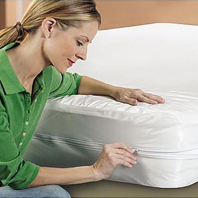 woman zipping up allergen free mattress covering