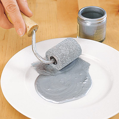 paint roller and silver paint on white plate