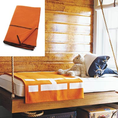 cabin style bedroom with orange wool blanket