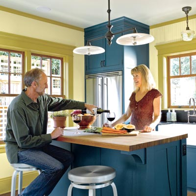 couple entertaining in kitchen with blue cabinets and olive walls