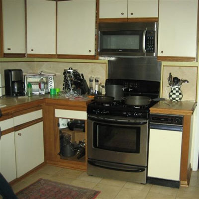 outdated kitchen with laminate cabinets and tile floors