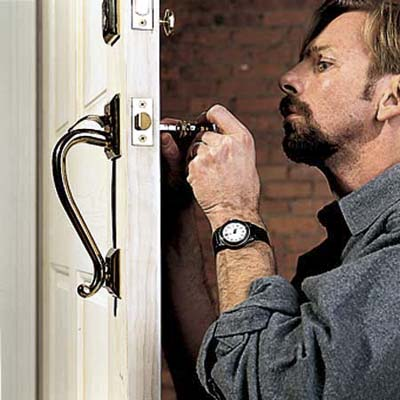 person using a tool to install a lockset in an interior door