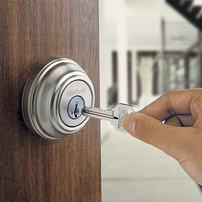 hand pushing a key into a door lock