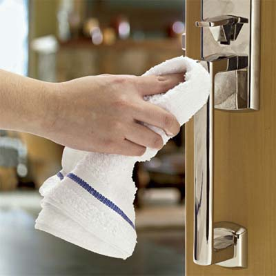 hand wiping down the handle of an entry set with a towel