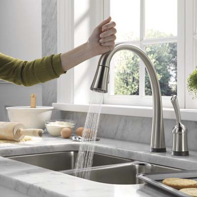 woman using touch activated kitchen faucet by delta