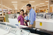 two adults and a baby shopping in an appliance showroom