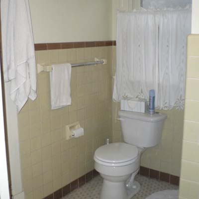 outdated bathroom with off white tile and white toilet