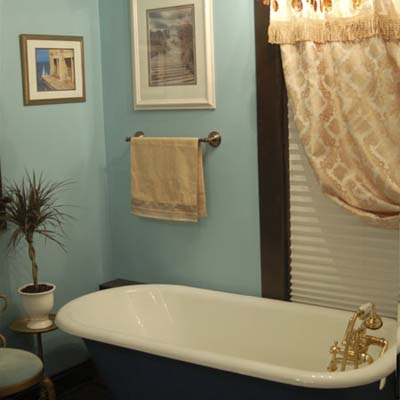 remodeled bathroom with blue walls and claw foot tub