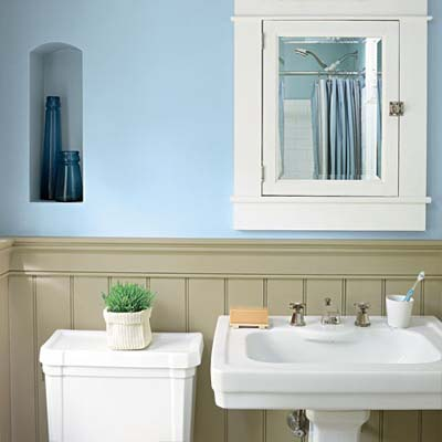 bathroom with blue walls and white cabinet, sink and toilet